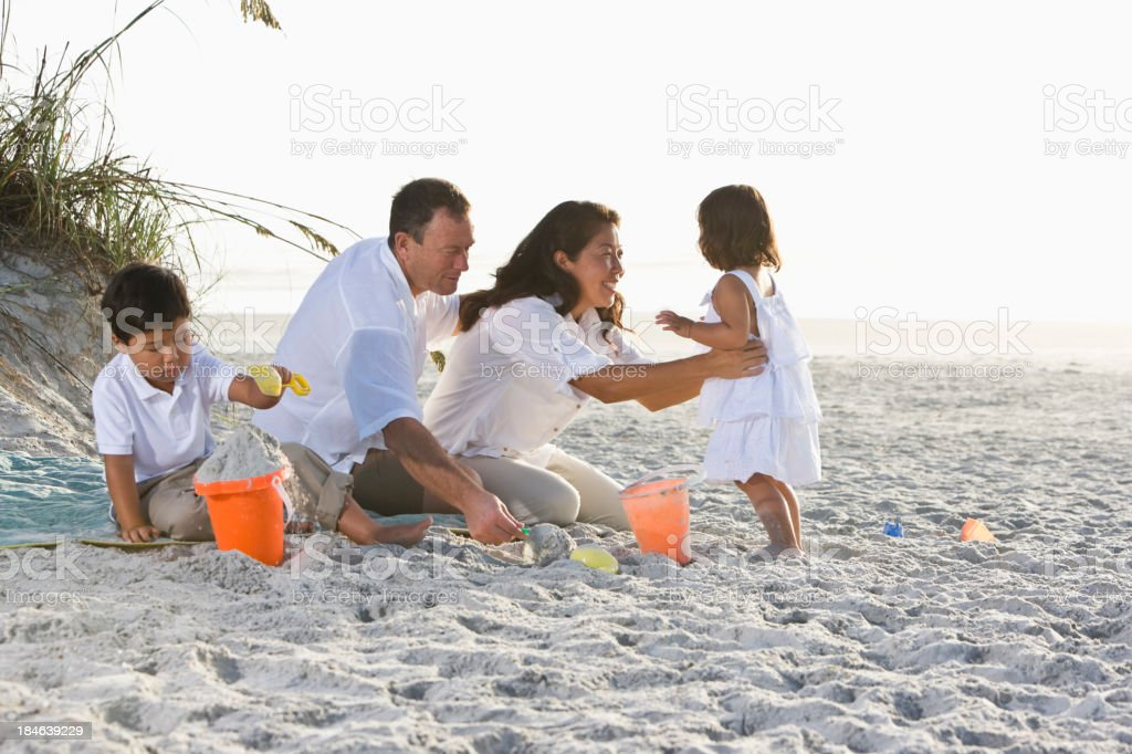 Interracial family with young children playing at beach royalty-free stock photo