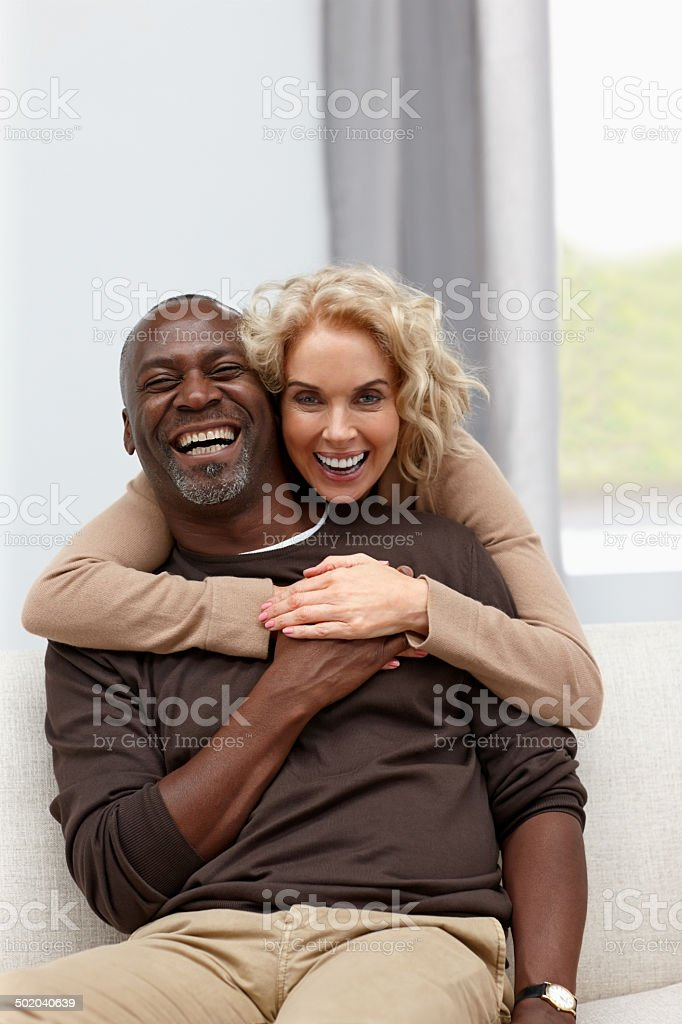 Interracial mature couple looking happy together stock photo