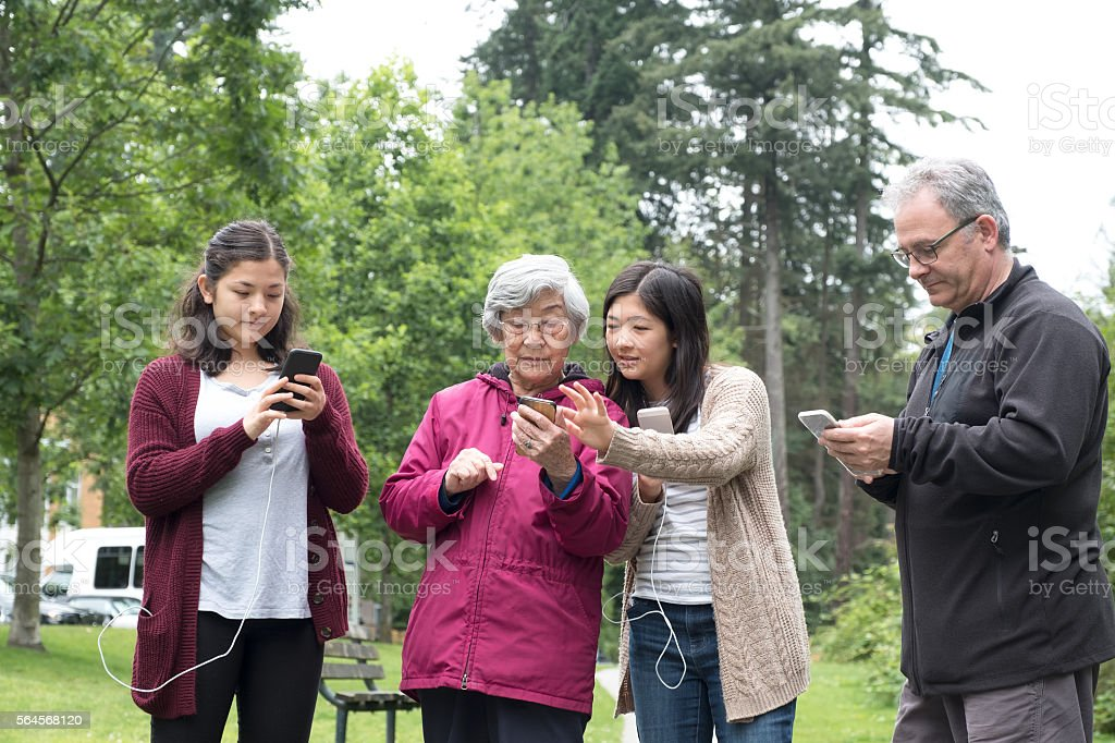 Interracial, Multi-Generational Family Playing Smartphone Augmented Reality Game in Park stock photo