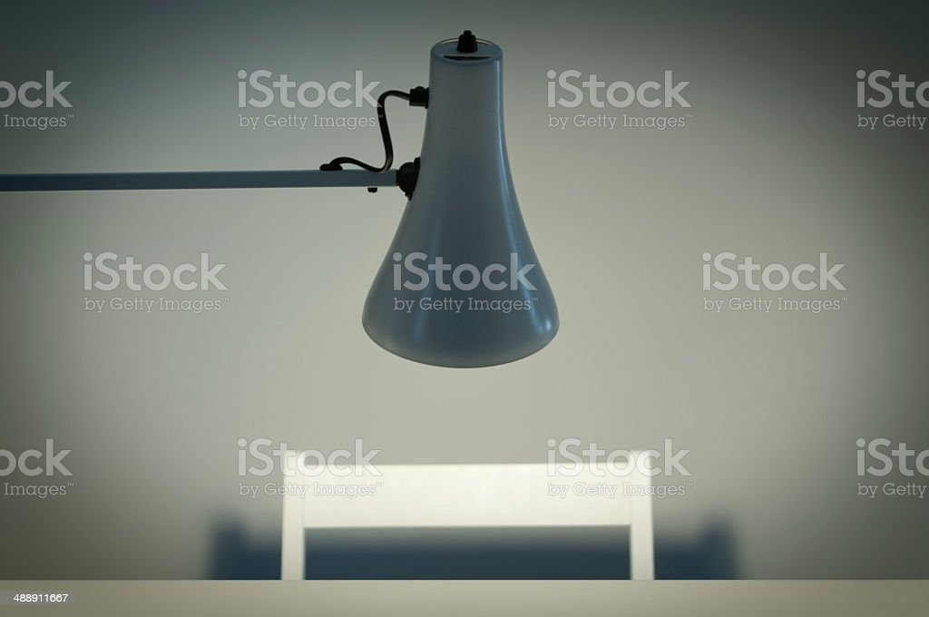 Interrogation chair and table with overhead light stock photo