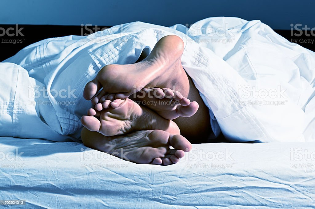 Intertwined feet of couple snuggling under white duvet stock photo