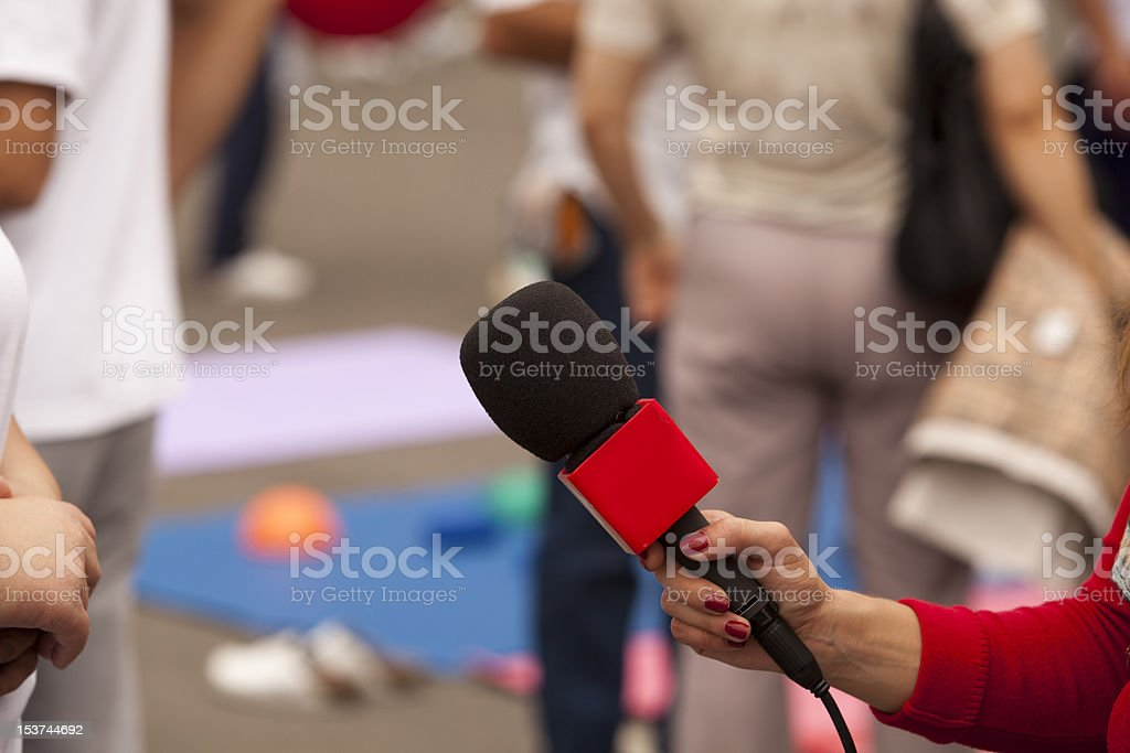 Interviewer presents microphone to their source stock photo