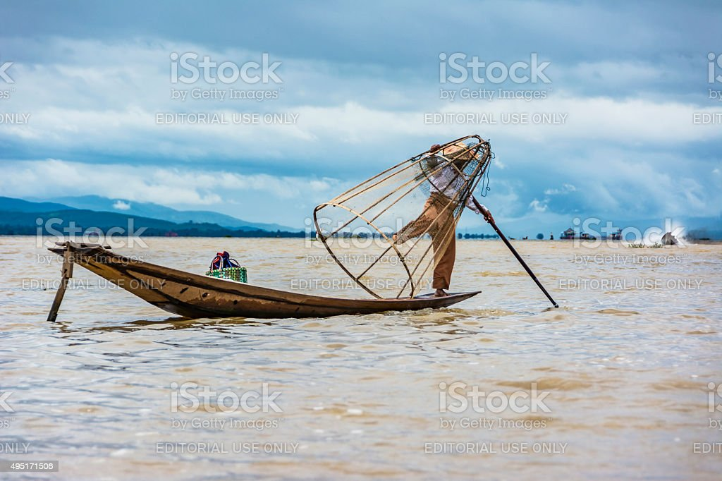 Intha fisherman fishing in his  canoe with fishing net stock photo