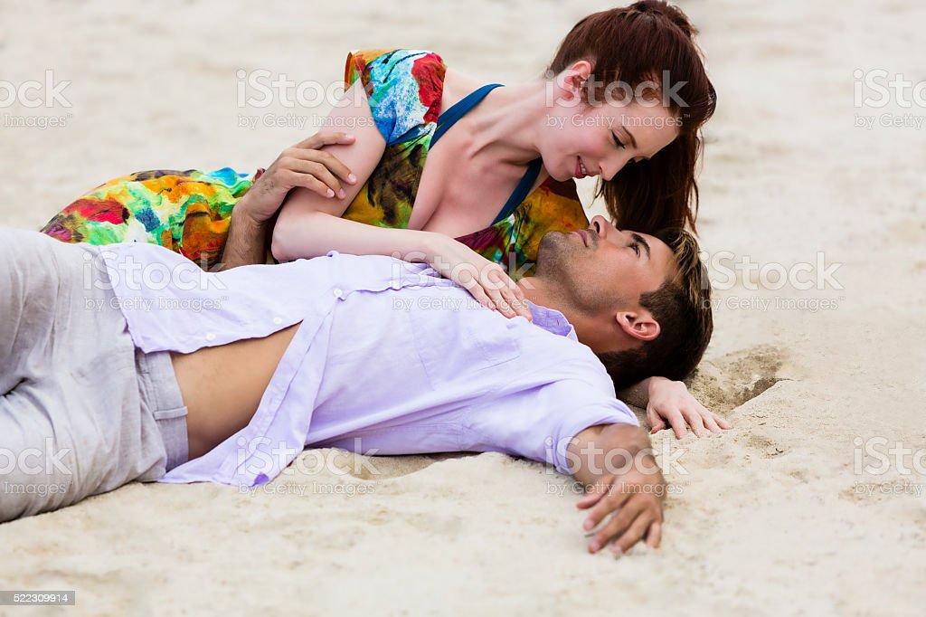 Intimate couple lying on sandy beach stock photo