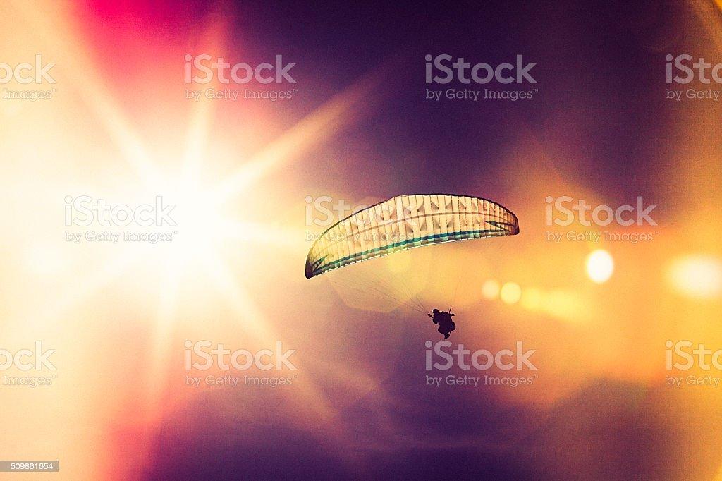 into the sun, paraglider silhouette stock photo