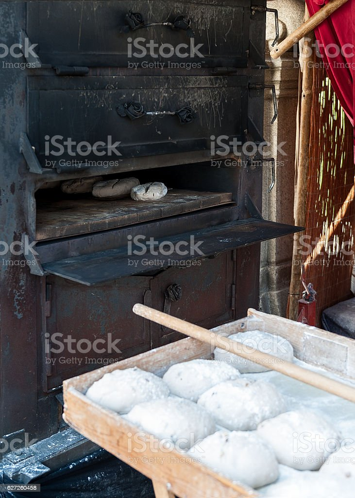 introducing artisan baker dough in the oven stock photo
