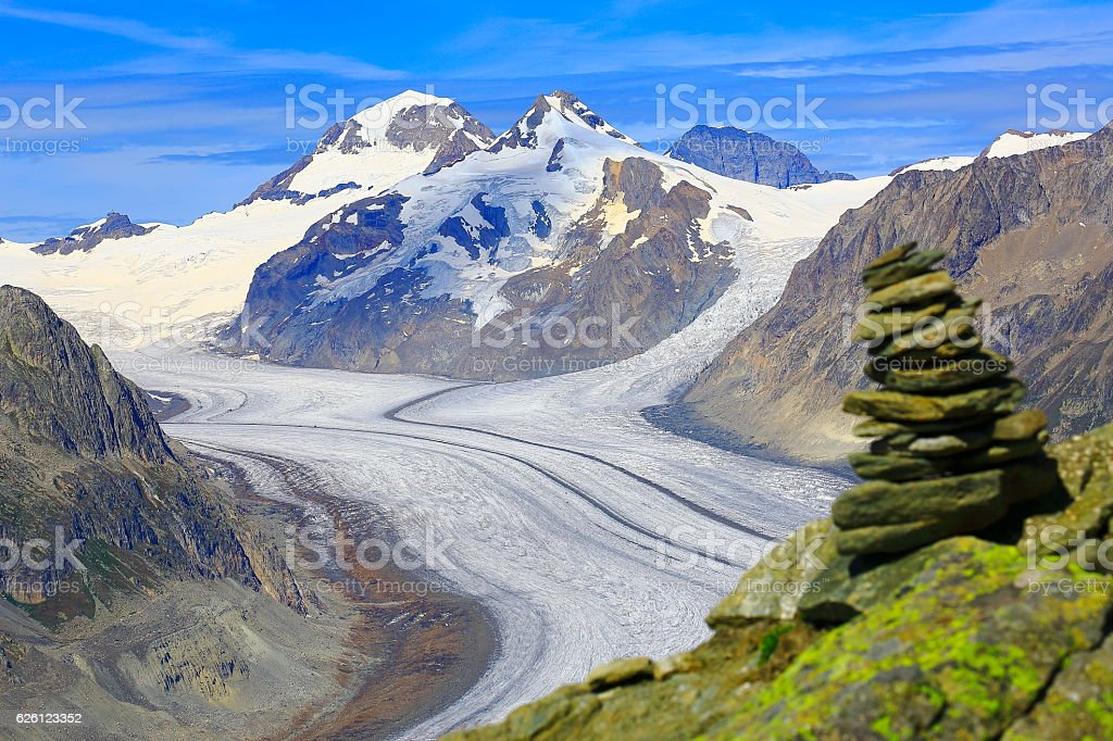 Inukshuk Above White Aletsch Glacier tongue crevasses , Valais, Swiss Alps stock photo