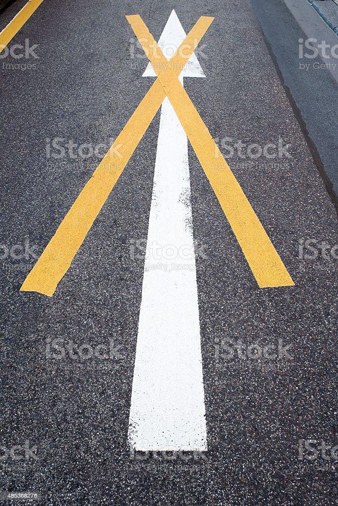 Invalid white road marking arrow, yellow cross stock photo