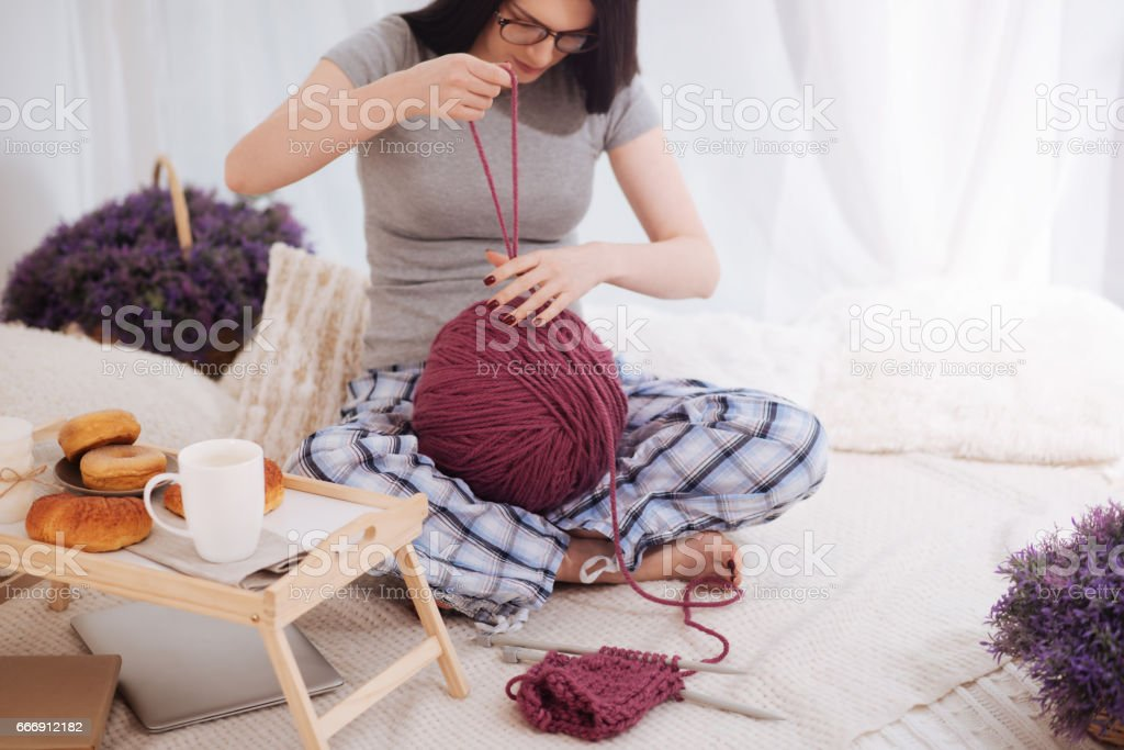 Inventive woman using ball of wool at home stock photo