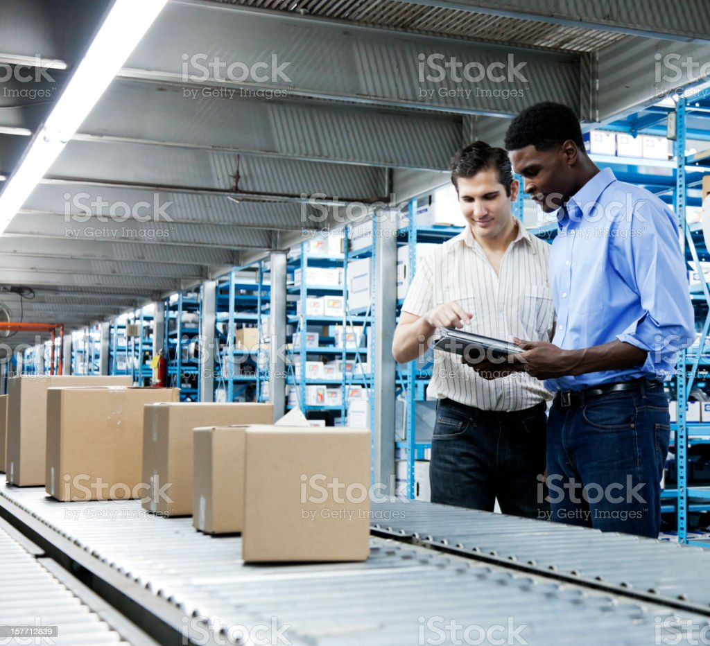 Inventory Inspection on Conveyor Belt with a Digital Tablet stock photo