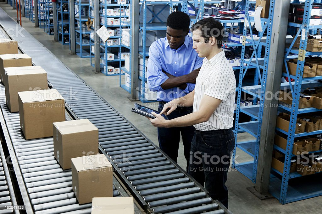 Inventory Inspection on Conveyor Belt with a Digital Tablet royalty-free stock photo