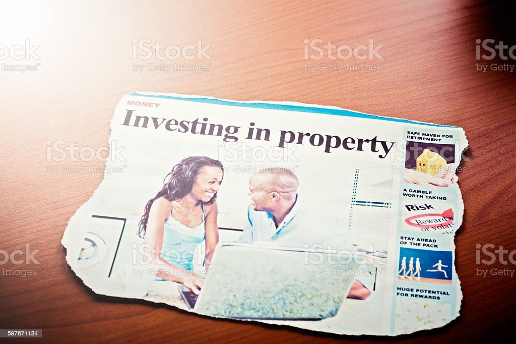 'Investing in property' article in newspaper illustrated by smiling couple stock photo