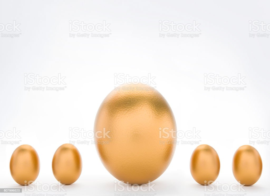 Investment Concept With Large And Small Golden Eggs stock photo