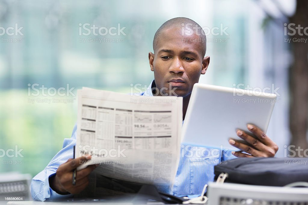Investor compares quotes from newspaper and tablet stock photo