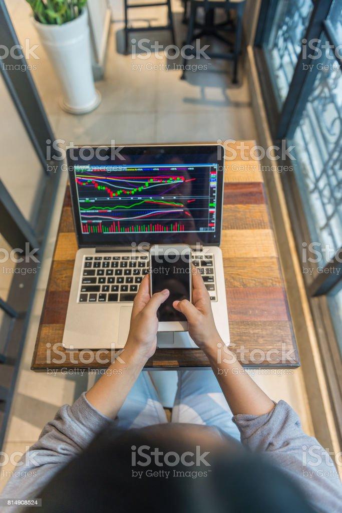 Investor using a smart phone analyze, update the stock market stock photo