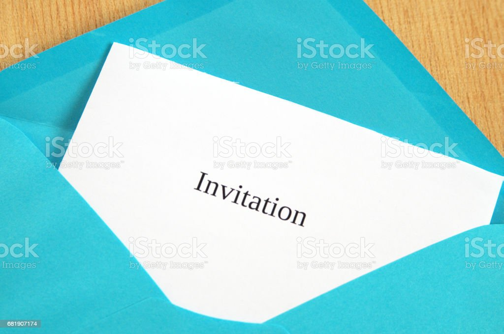 Invitation card printed on white paper in blue envelope, wooden background stock photo