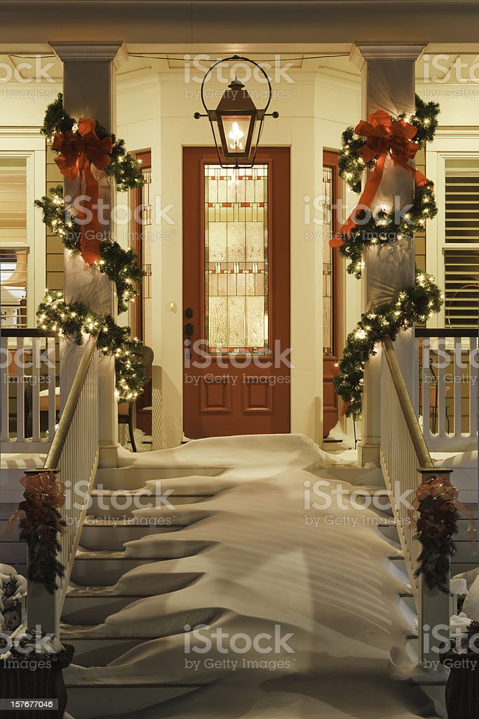 inviting Christmas home doorway with snowy porch at night stock photo