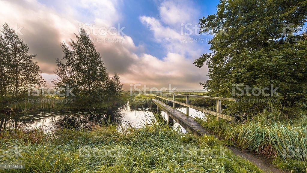 Inviting Footbridge  crossing river stock photo