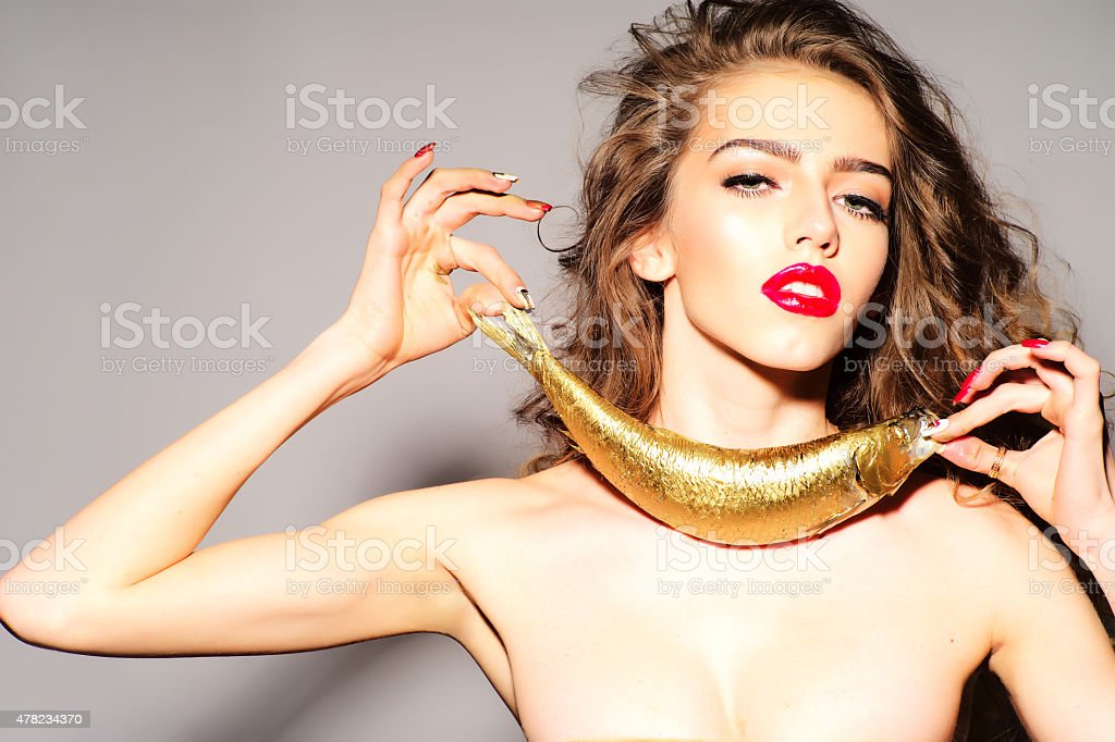 Inviting young naked woman with golden fish stock photo