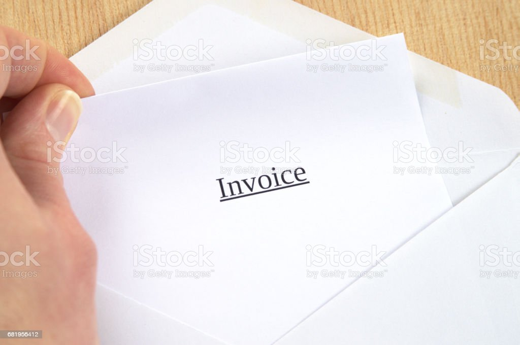 Invoice printed on white paper and envelope, hand holding it, wooden background stock photo