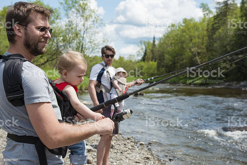 Involved dads and babys fishing in a sunny day royalty-free stock photo