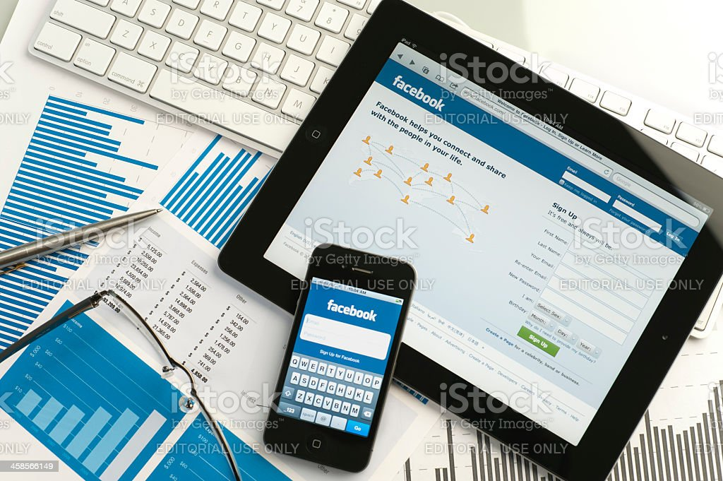 Ipad and iphone on a desk showing facebook stock photo