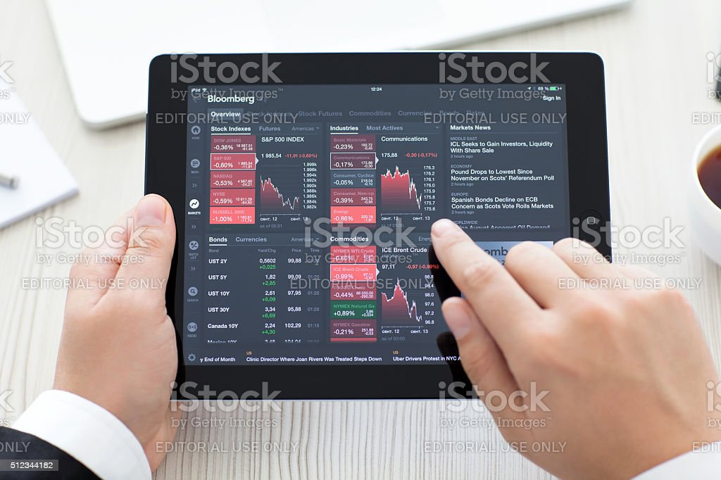 iPad with app Bloomberg in the hands of a businessman stock photo
