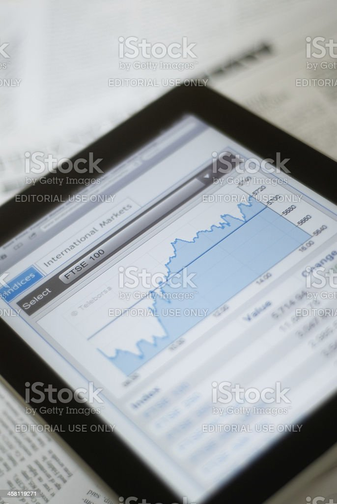 Ipad with stockmarket graph stock photo