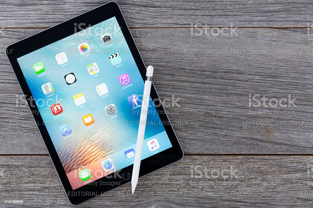 iPadPro (9.7 inch) SpaceGrey Isolated on Wood With Apple Pencil stock photo