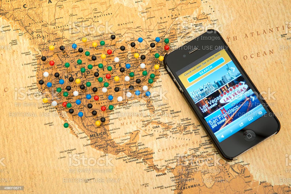 Iphone 4 with Booking.com travel application on map of USA. royalty-free stock photo