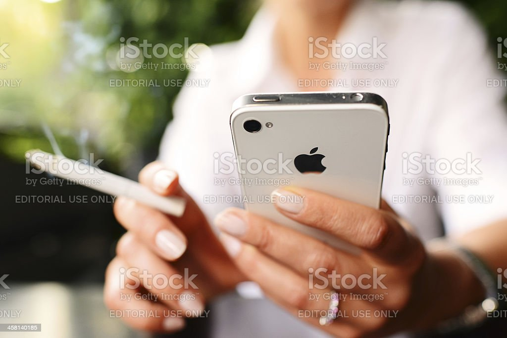 iPhone 4s and cigarette in woman hands royalty-free stock photo