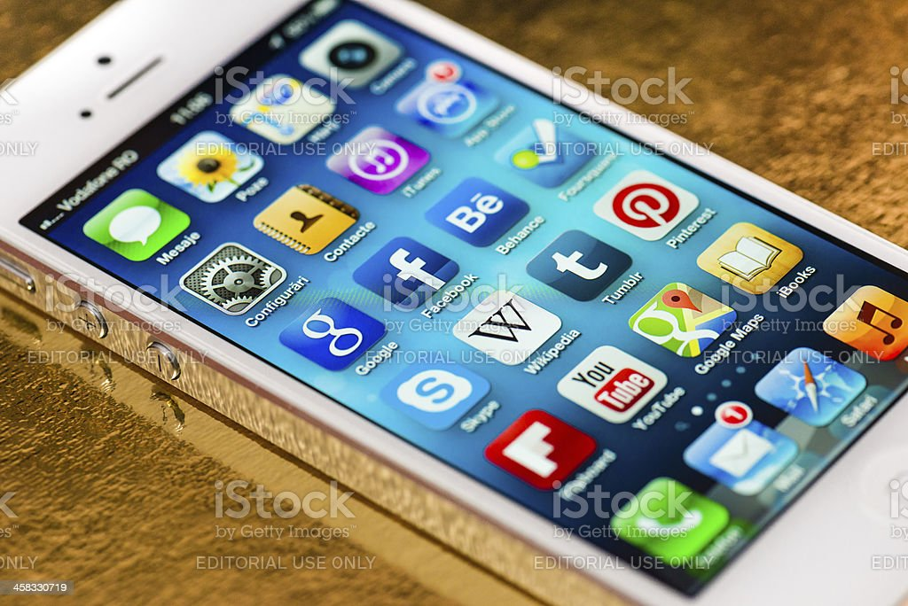 iPhone 5 Apps screen on a golden surface stock photo