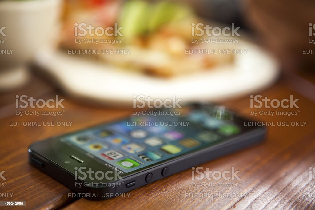 iPhone 5 on table in cafe royalty-free stock photo