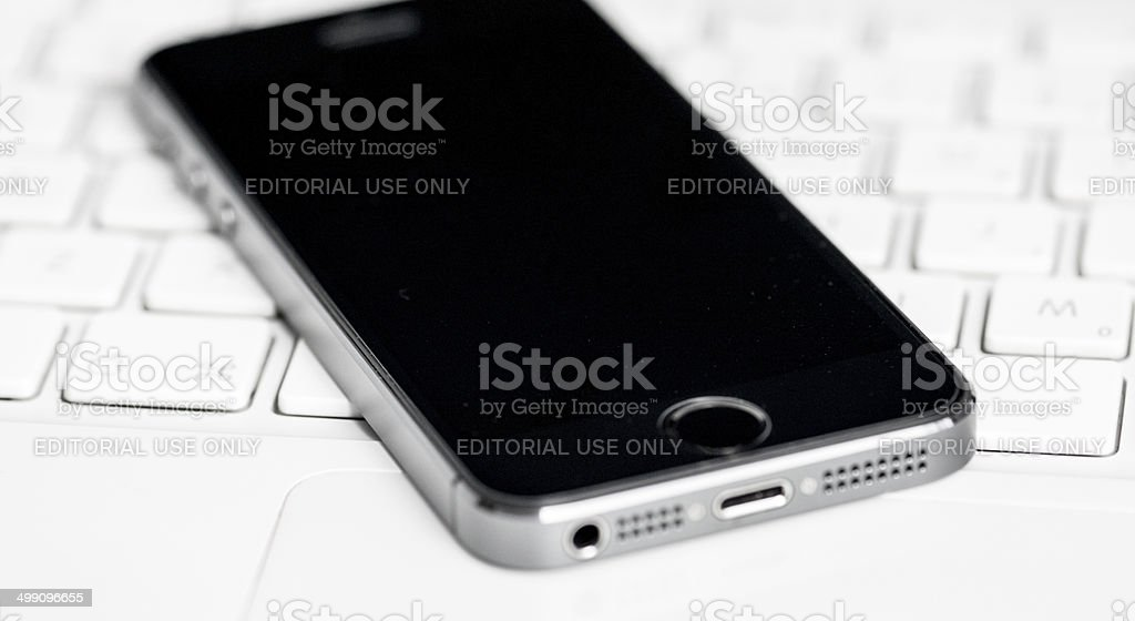 iPhone 5s on a white Apple computer keyboard royalty-free stock photo