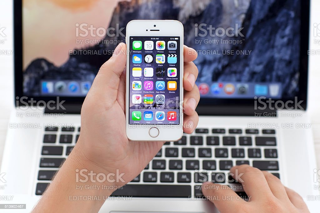 iPhone 5S with IOS 8 in hand over MacBook Pro stock photo