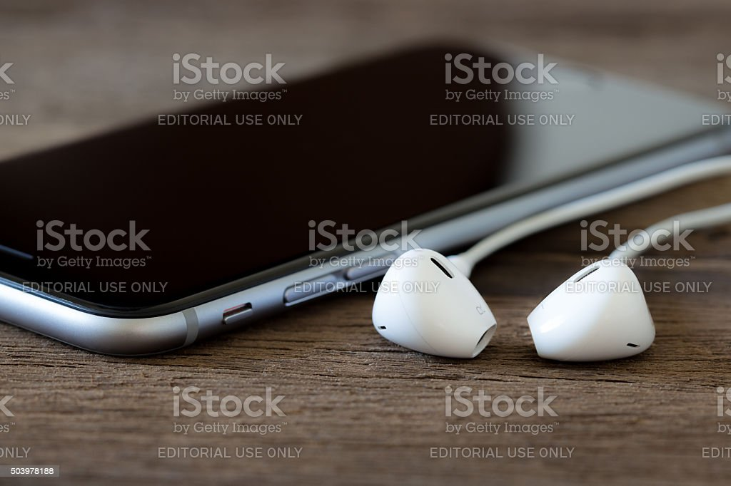 iphone 6s black color and headphone on wood desk stock photo