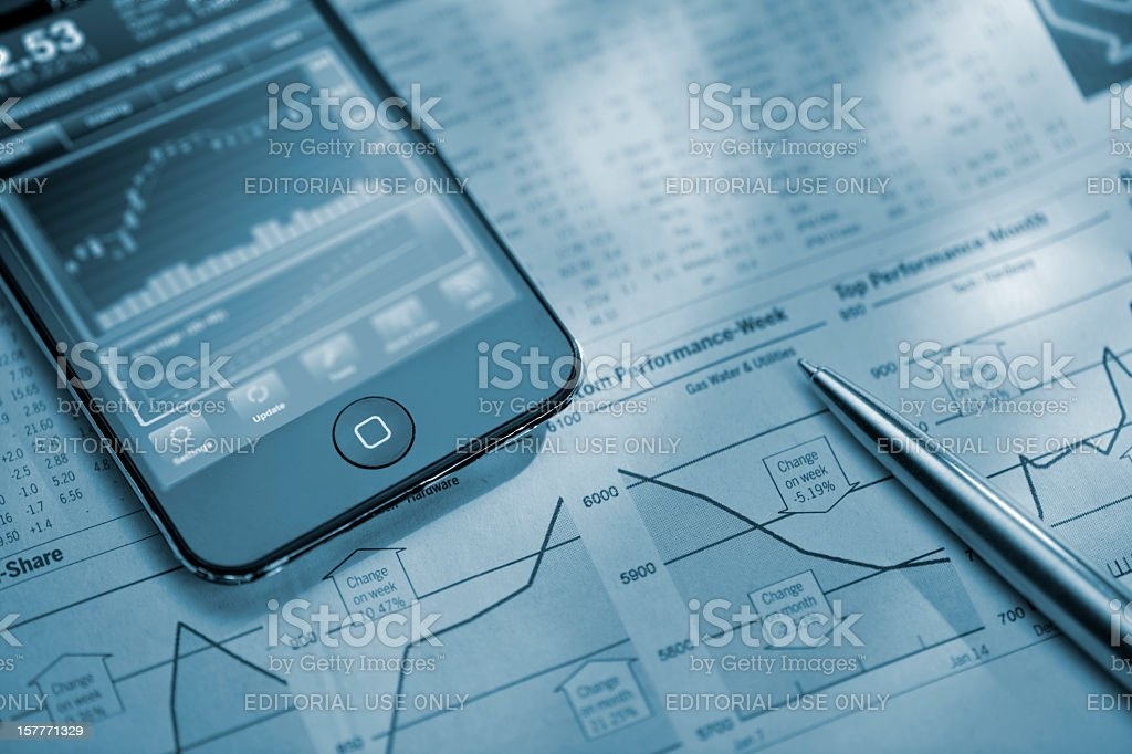 iphone on financial newspaper royalty-free stock photo