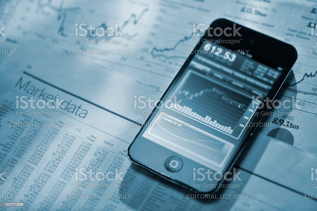 iphone on financial newspaper stock photo