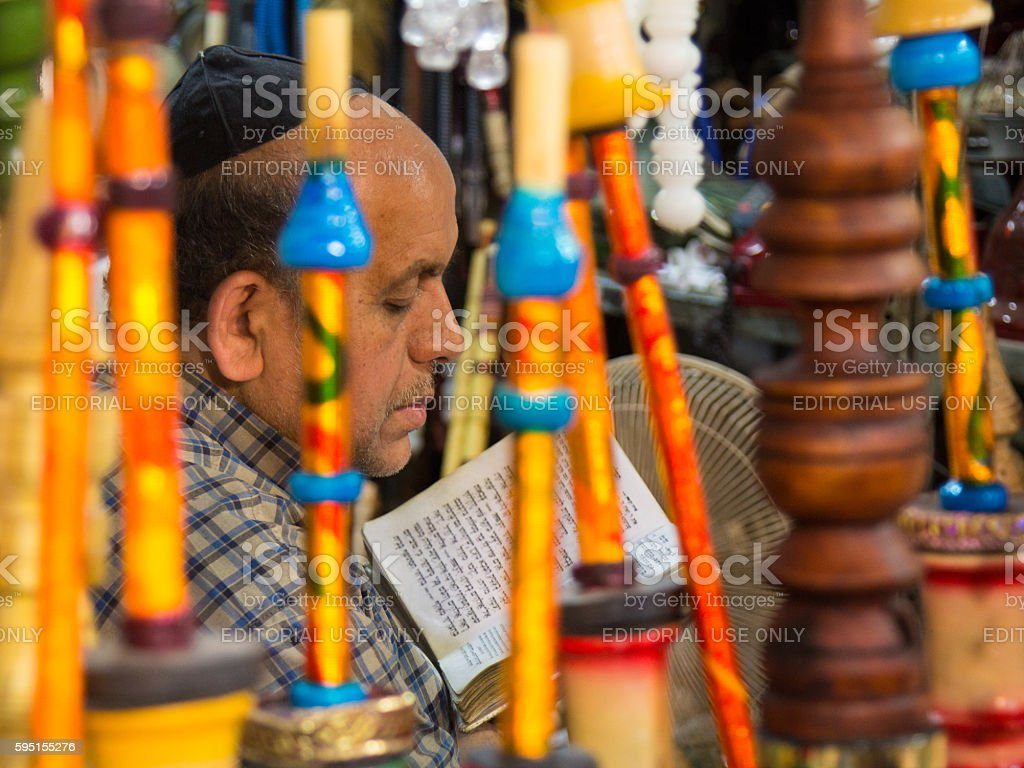 Iranian Jewish waterpipe seller reading the Torah in his shop stock photo