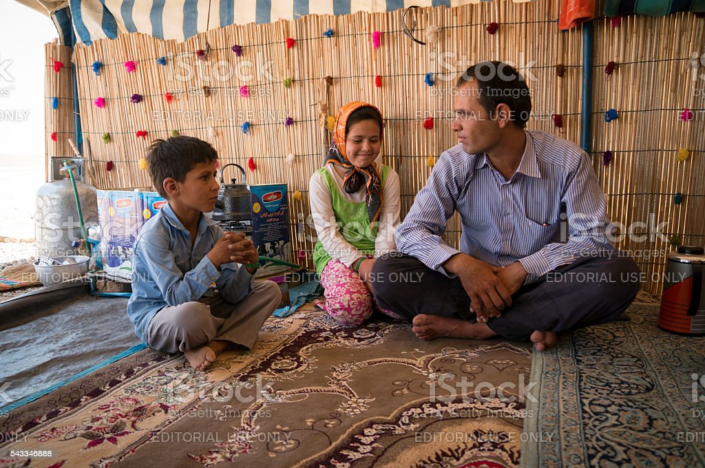 Iraninan nomad family sitting inside their tent stock photo