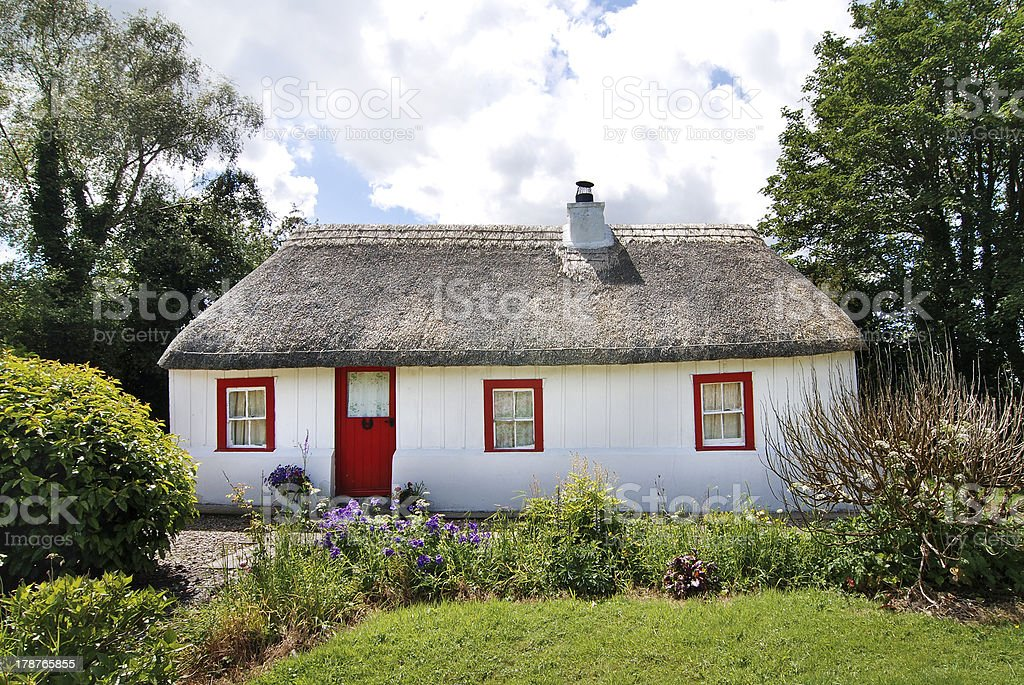 Irish cottage with straw thatched roof and lush garden stock photo