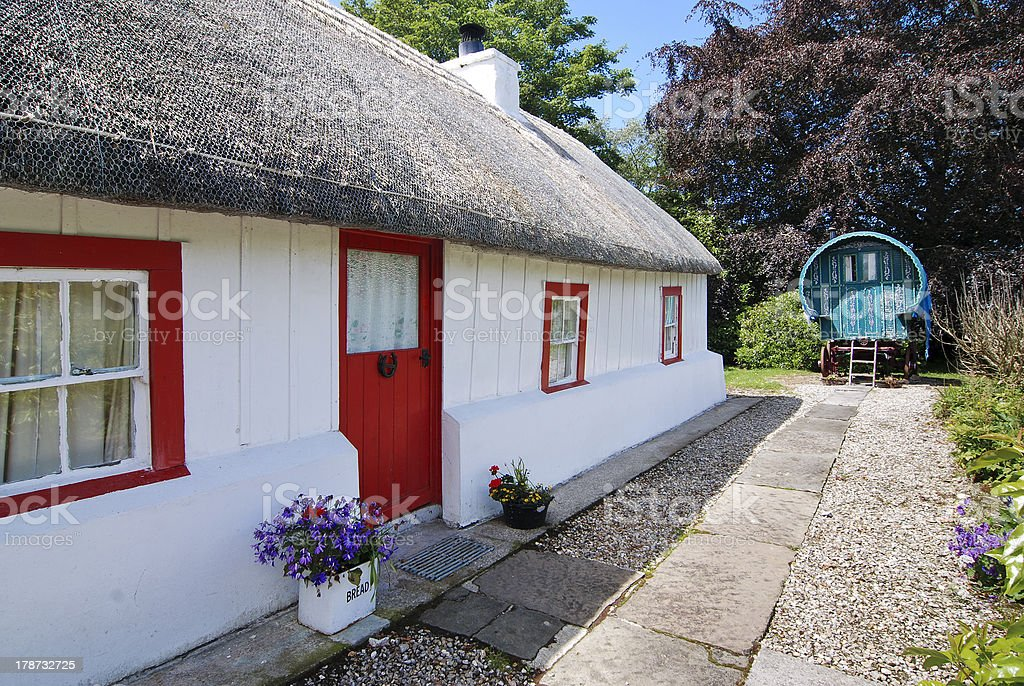 Irish cottage with straw thatched roof and romany gypsy caravan royalty-free stock photo