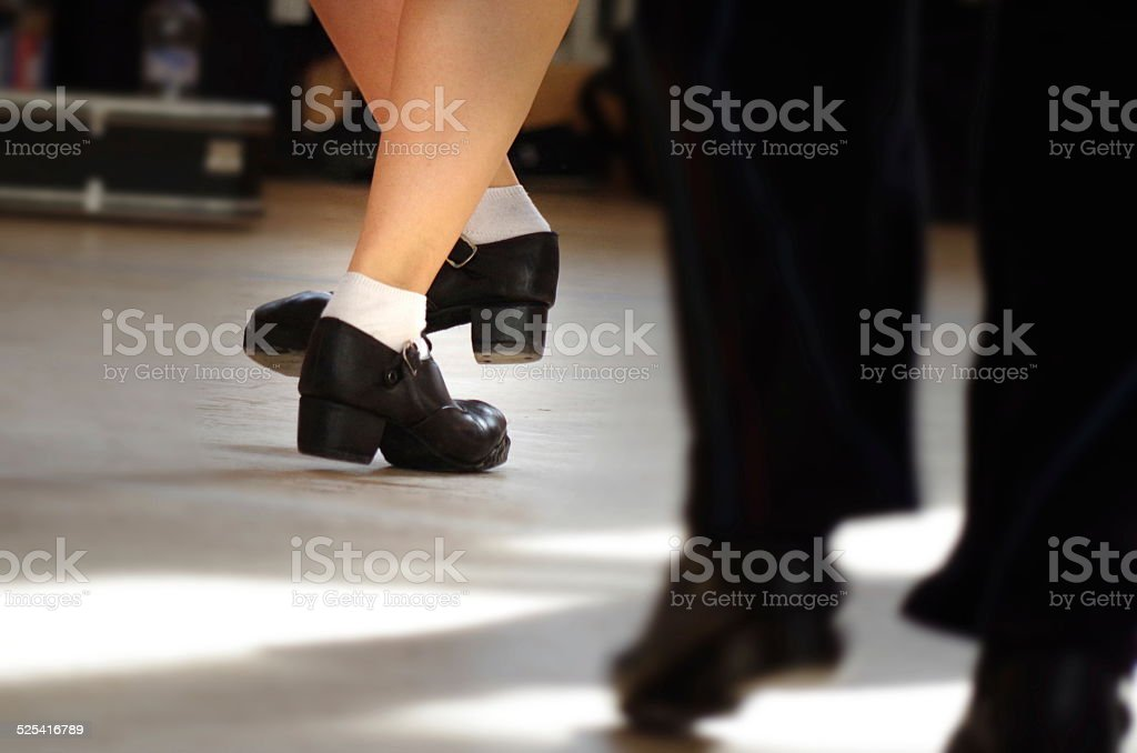 Legs of male and female irish dancers in hard shoes .