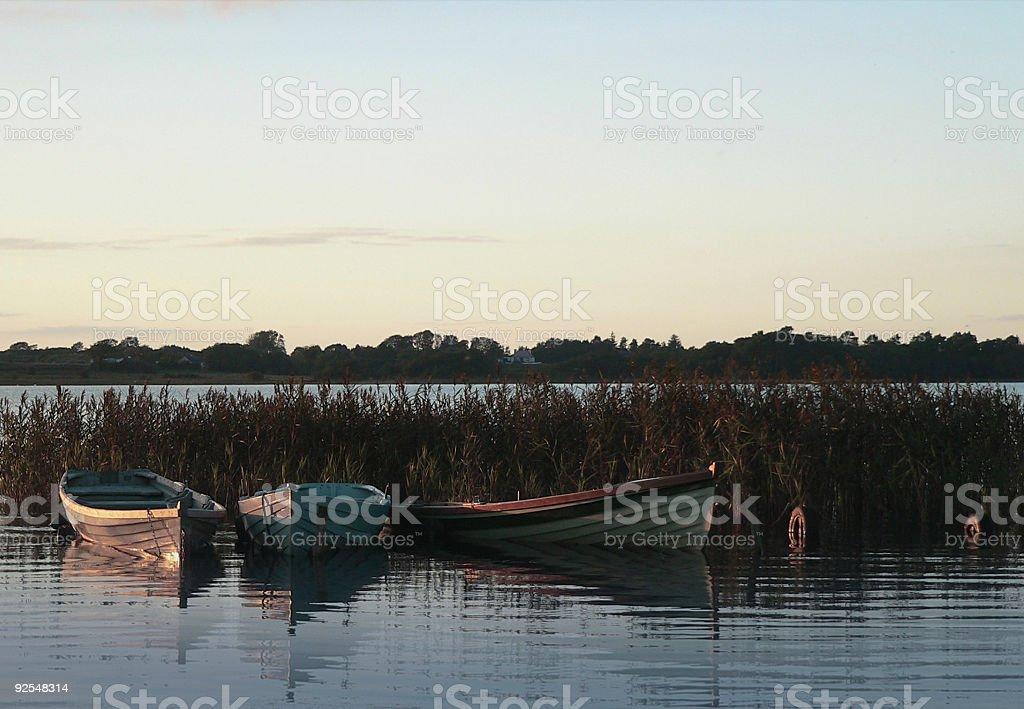 Irish lake with three wooden rowing boats at sunset royalty-free stock photo
