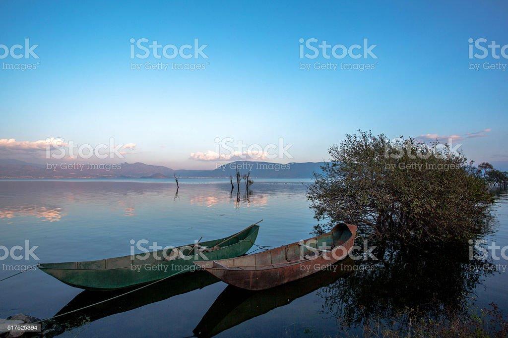 iron boat on lake, at sunset stock photo