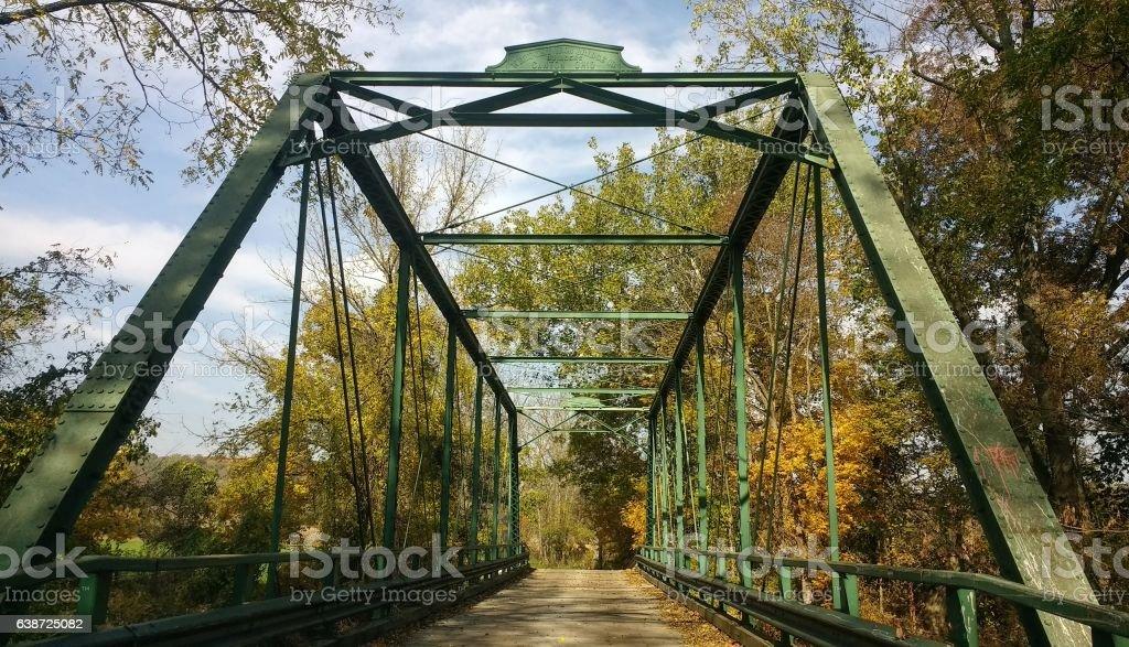 iron bridge on old country road with autumn foliage stock photo