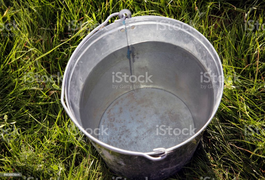 Iron bucket with pure water on a background of a green grass stock photo