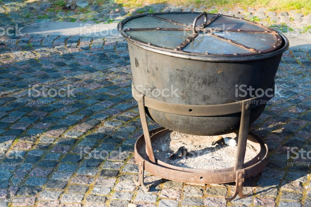 iron cauldron with a fire chamber for cooking stock photo
