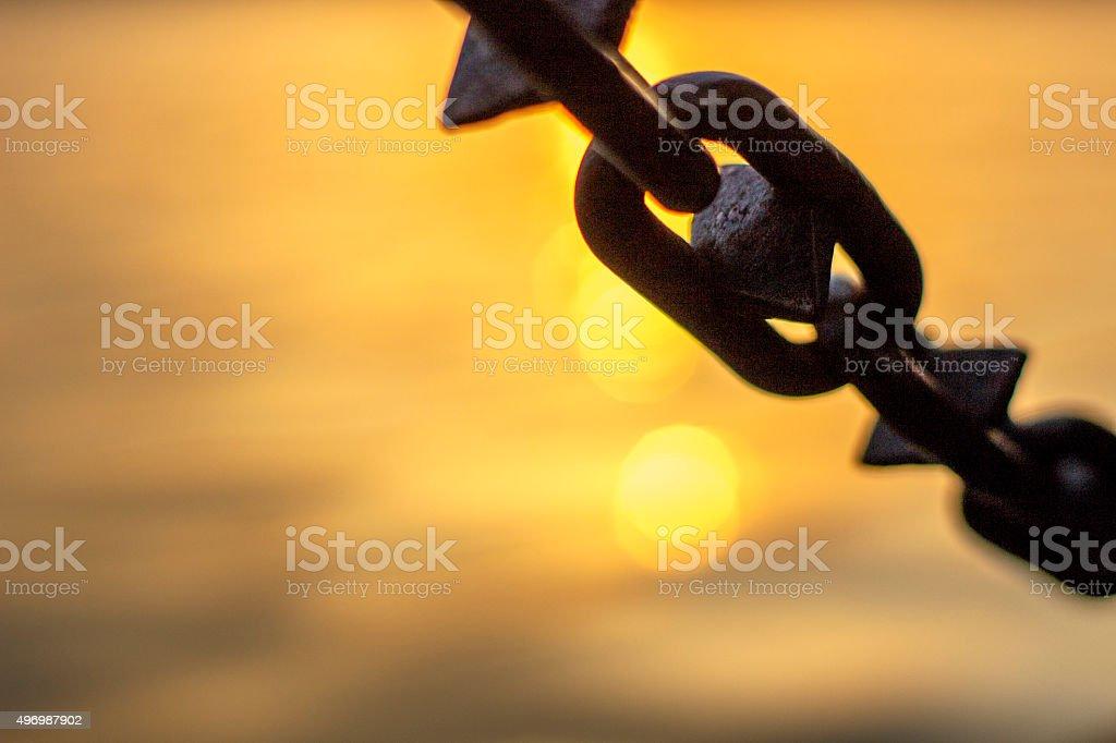 iron chain railings beside lake at sunset stock photo