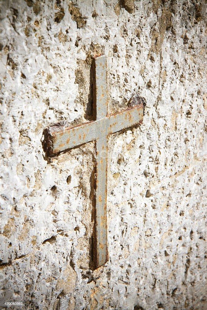Iron cross snuggled in stone stock photo